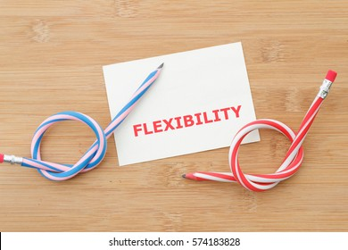 Flexible red and blue rubber pencil on wooden background with word FLEXIBILITY
