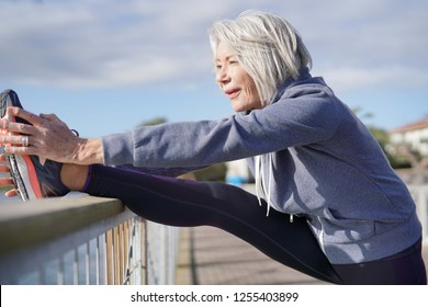 Flexible senior woman stretching outdoors after jog