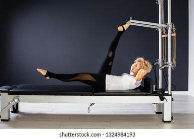 flexible and slim female using Pilates reformer machine in gym