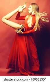 Flexible straight young fashionable woman with long beautiful hair in red elegant dress holding raised leg in glamour golden shoes licking heel with tongue on pink background, vertical picture