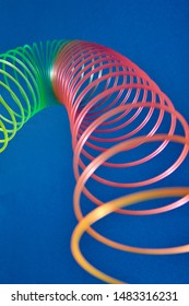 Flexible stretching multicolored slinky toy close up view with blurred foreground, place for text.