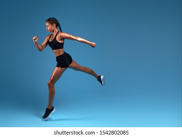 flexible strong slim sportswoman running over blue background. lifestyle, free time, spare time, copy space. isolated blue background, studio shot
