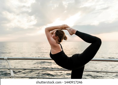 Flexible woman doing yoga asana near the sea on sunrise in the morning, practicing sport and fitness exercises