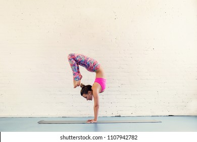 Flexible woman doing yoga exercise in studio. White brick wall on background