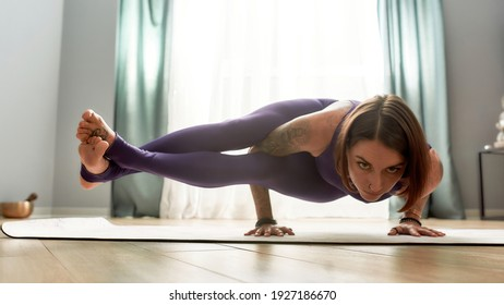 Flexible woman in tight sportswear looking focused, practicing yoga, doing Eight Angle pose while exercising in living room at home on a daytime. Fitness, relaxation, stay home concept. Web Banner
