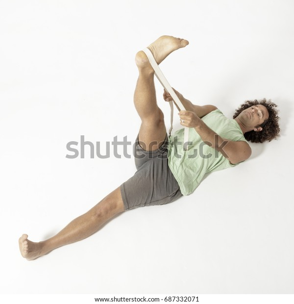 flexible yoga man in supta padangustasana reclined lying down with belt pose