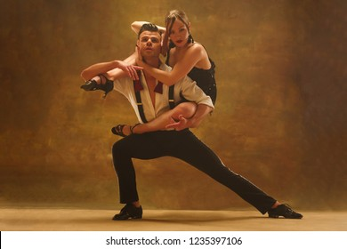 Flexible young couple dancing pasadoble in studio. Fashion portrait of attractive man and woman. Passion. Love