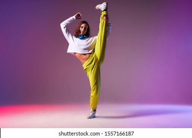 Flexible young dancer dressed in brightly coloured clothes, raising leg up, doing split leap in the air, work out of professional dancer, studio background