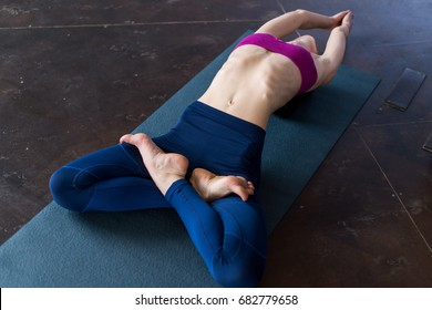 Flexible young woman lying on floor doing stretching exercise for body raising chest up with her legs in lotus pose