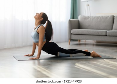 Flexible young woman in sportswear practicing yoga at home, laying on yoga mat in living room and stretching her body, side view, copy space. Yoga pose, yoga practice at home concept