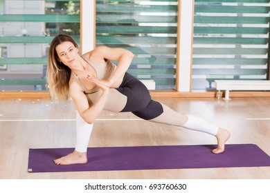 Flexible young woman stretching her right leg in gym.