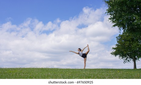 Flexible young woman in a yoga pose outdoors