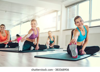 Flexible young women stretching together and smiling