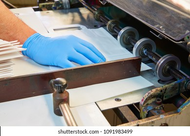 Flexo printing machine in a print factory operator hand detail