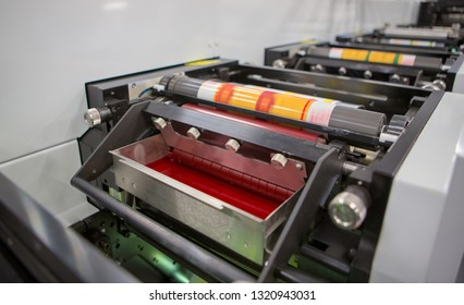 Flexographic printing machine with an ink tray, ceramic anilox roll, doctor blade and a print cylinder with polymer relief plate stuck on it. In-line press machine. Rotary or Flexo printing machine.