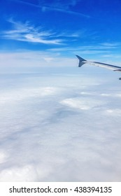 Flight with Airplane - window view with wing over the clouds.