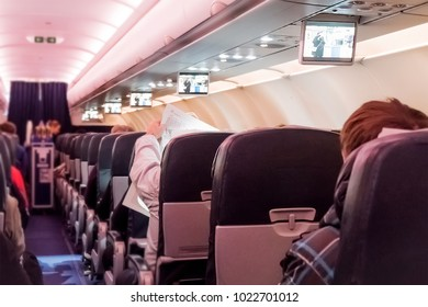 A flight attendant distributes food in economy class. Interior of large passengers airplane with people on seats. Blurred background. Focus on the seat.