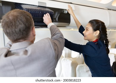 flight attendant helping passenger with carry on luggage to overhead bins