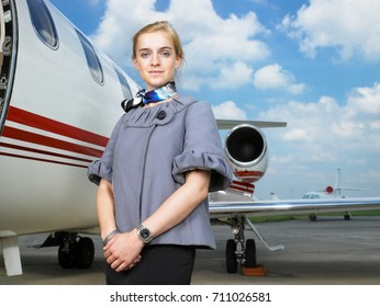 Flight attendant next to private jet.