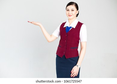 Flight attendant in a red vest gesticulates hands