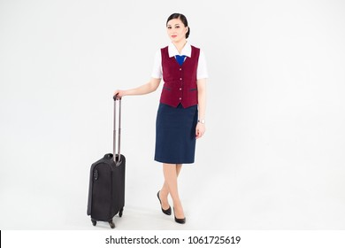 Flight attendant in a red vest stands with Luggage