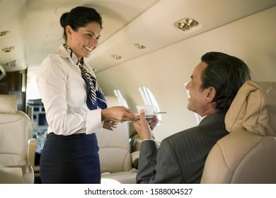 Flight attendant serving drink to businessman on airplane