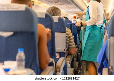 Flight attendant serving drinks to passengers on board