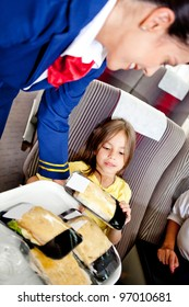 Flight attendant serving food to a kid in the airplane
