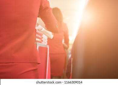 flight attendant serving food to passenger on aircraft. stewardess offer drink on board. hostess with trolley on aisle