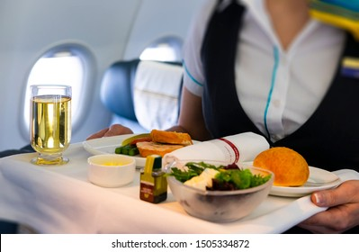 flight attendant serving meal in an airplane