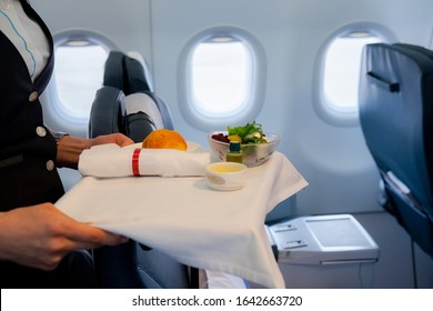 Flight attendant serving meal to passengers on board.