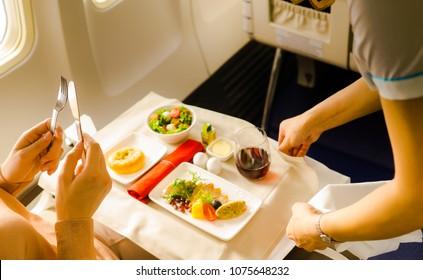 Flight attendant serving a passenger in an airplane
