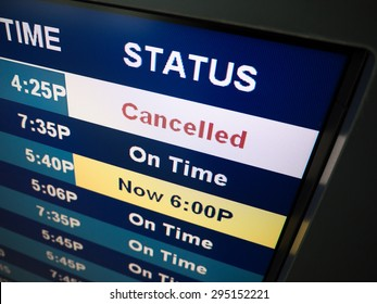 Flight cancelled. Airport arrival and departure board sign showing on-time and cancelled flight status