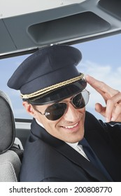 Flight captain saluting in airplane cockpit