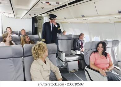 Flight captain standing in between passengers of business class airplane cabin