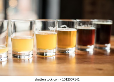 Flight of craft beers in small pint glasses, arranged in a diagonal row with ascending volumes, at a local brewery