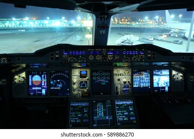 Flight deck of civil wide body airplane at night.