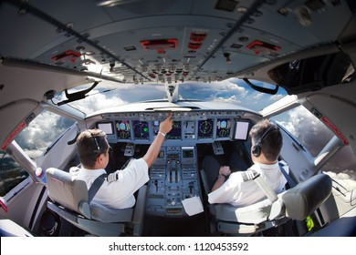 Flight Deck of modern aircraft. Pilots at work. Clouds view from the plane cockpit.