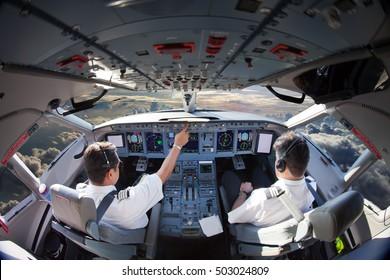 Flight Deck of modern passenger aircraft. Cockpit view in flight during the sunset. Aircraft Pilots at work.