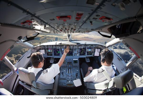 Flight Deck moderner Passagierflugzeuge. Cockpit-Ansicht im Flug während des Sonnenuntergangs. Flugzeugpiloten bei der Arbeit.