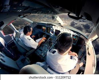 Flight Deck of modern passenger jet aircraft. Pilots at work. Cloudy sky and sunset view from the plane cockpit.