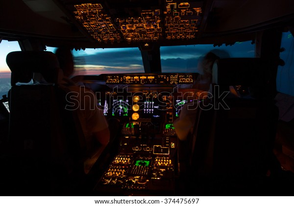 Flight Deck of modern passenger jet aircraft in the night. The pilots in the airplane cockpit are greeted sunrise.