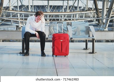 flight delay or problem in the airport, tired desperate passenger waiting in the terminal with suitcase