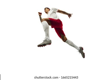 Flight. Football or soccer player on white background with grass. Young male sportive model training. Attacking, catching. Concept of sport, competition, winning, action, motion, overcoming. In jump.