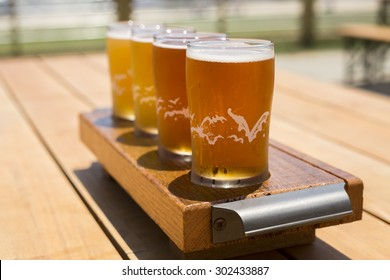 Flight of Golden Beers on Bright Summer Day. A flight of golden and amber beers on a wooden plank. The drinks are on a picnic table outside on a bright summer day.