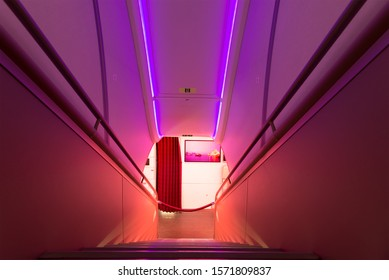 In Flight / International Airspace - March 16 2018: Qatar Airways Airbus A380 stairs connecting the luxury First and Business Class cabins. Beautiful illumination, handrail, and rope blocking access.