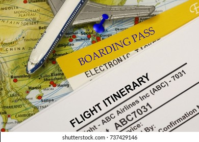 Flight Itinerary with boarding pass and airplane model toy - concept for travel.