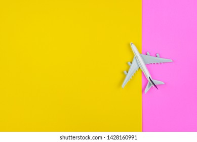 Flight itinerary / travel plan schedule, tourism concept : Airplane or aircraft lands on pink-yellow background, depicts preparation for oversea business round trip on cheap, budget reservation ticket
