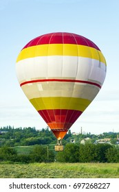 Flight of large air balloon over green field against blue sky