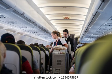 Flight Lisbon-Funchal, August 26, 2018: Stewardess and steward carry food and drinks in the cabin.